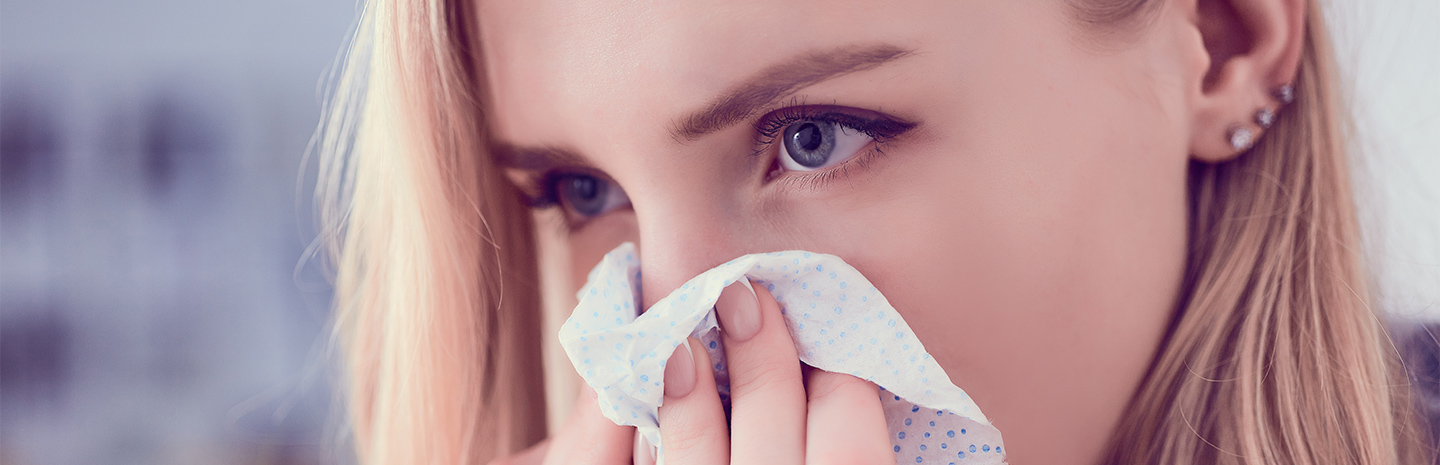 woman-blowing-her-nose-into-tissue